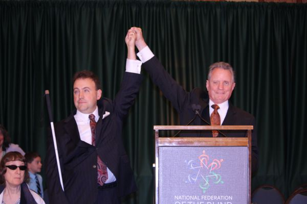 NFB President Mark A. Riccobono raises hands with Immediate Past President Marc Maurer at the 2014 National Convention.