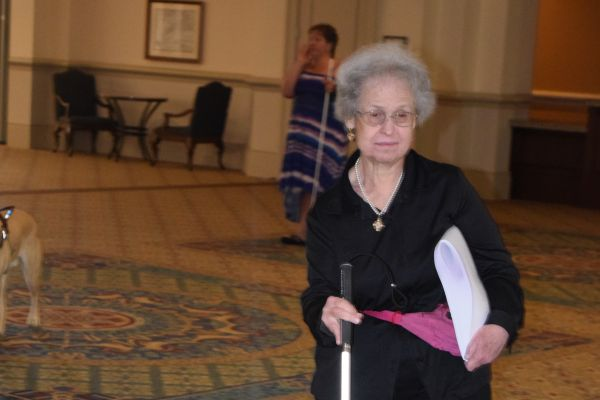 A woman with a white cane walks to a session at the NFB National Convention.