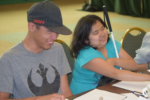 Two students in the 2018 NFB EQ program smile during a workshop.