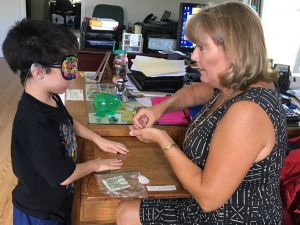 A boy wears sleep shades and exchanges money with an NFB BELL Academy instructor.