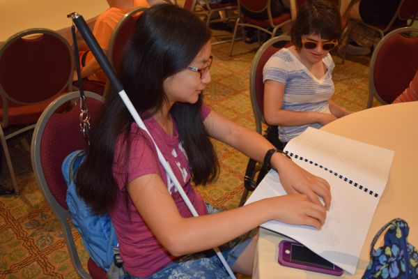 A girl with a white cane sits at a table and reads from a Braille book.