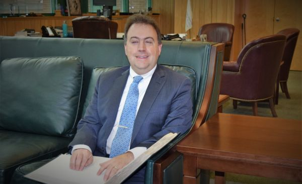 NFB President Mark A. Riccobono sits on a couch and reads from a Braille book.