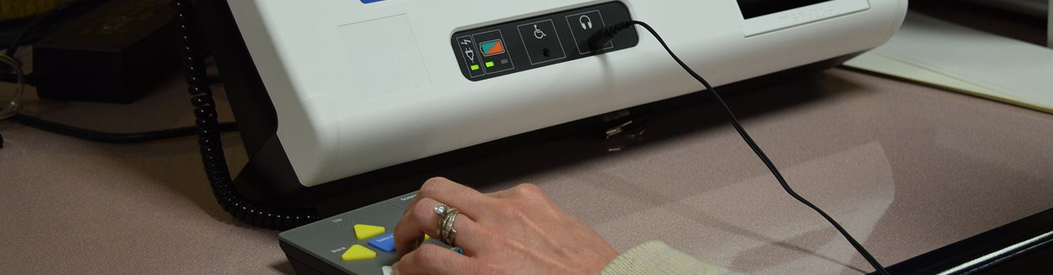 A woman's hand presses buttons on the Brailled keypad of a BMD; a headphone cord comes out of a headphone jack on the machine.