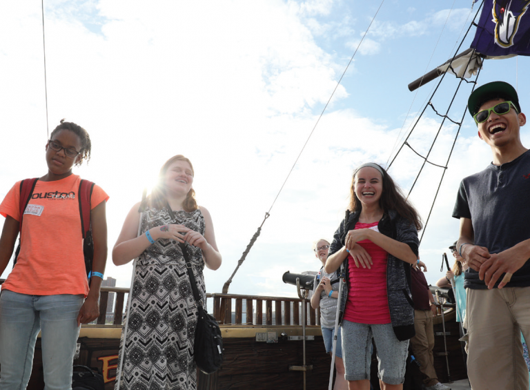 Five teenagers, two with white canes, smile and laugh on the deck of a boat.