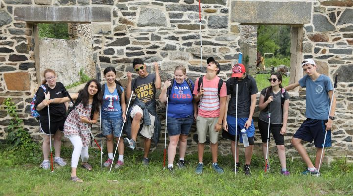 Students stand outside against a stone wall during the 2018 NFB EQ program.