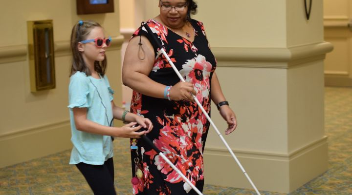 A blind woman and a blind girl walk with white canes.